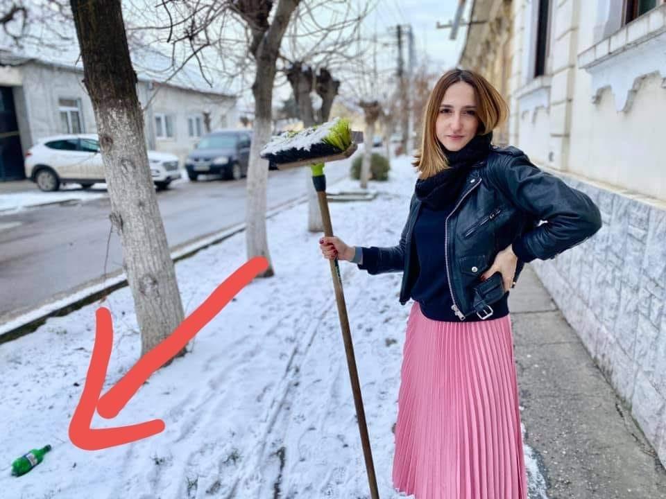 Consilierul local USR, Ana Munteanu, echipată corespunzător pentru deszăpezirea trotuarului, cu pliuri roz și geacă de piele, sprijinită intr-o coada de matură, nu de lopată, alături de un pet de bere de toată frumusețea, chiar sub geamul locuinței.